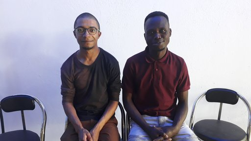 An African American male Peace Corps volunteer and a South African male sit together on folding chairs.