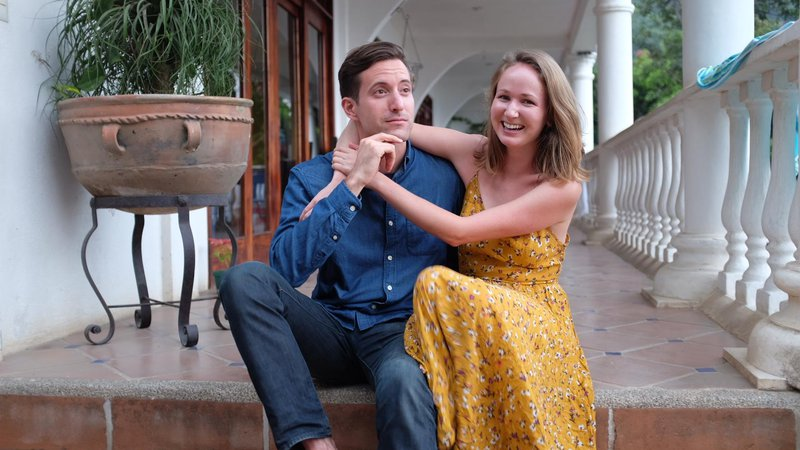 Two Peace Corps Volunteers sit on tiled steps. They are leaning on each other and smiling.