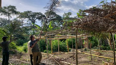 community members and Volunteer Logan build the cocoa nursery structure