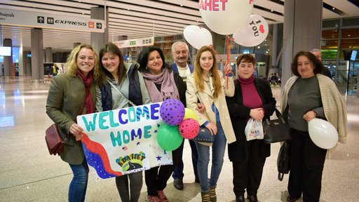 Emily and her community members waiting for the boys' arrival at the airport