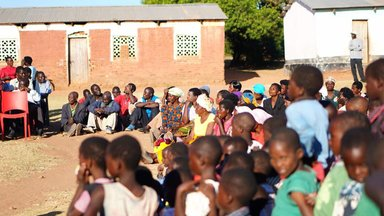 Women, men, and children gather together outside of a school house.