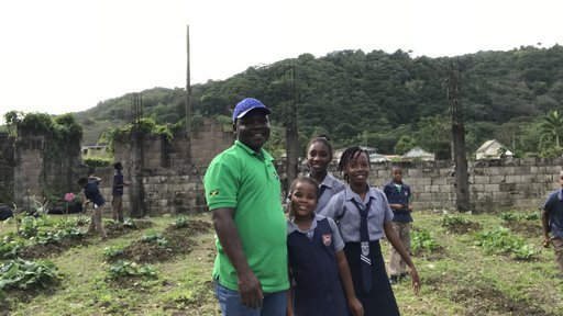 Male Peace Corps Jamaica volunteer from Togo spends time in the garden with his primary school students