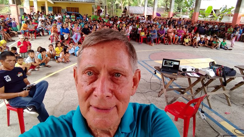 An older American white male takes a selfie in front of a large group of his primary school students and fellow teachers.