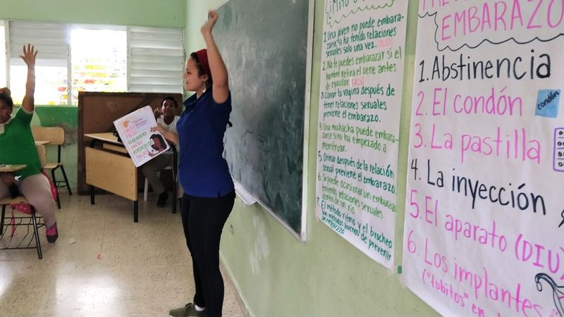 Volunteer Ashley stands in the front of a classroom and raises her hand to encourage student participation.