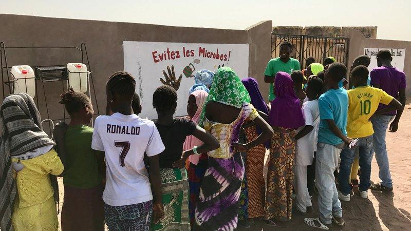 Badara Drame instructs the children on the importance of handwashing.jpg