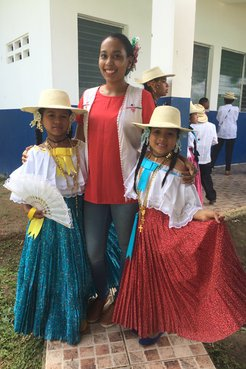 Latinx Volunteer in jeans poses with two young Panamanian girls in traditional dress.