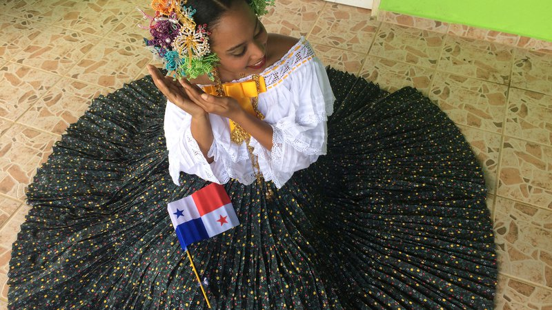 Latinx Volunteer dressed up in a pollera, a long Panamanian skirt.