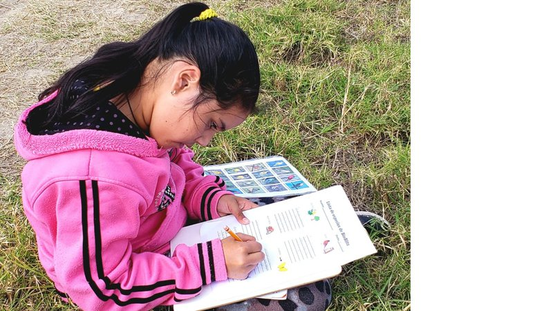 Araceli sits in the grass, making notes of the flora and fauna around her on a clipboard.