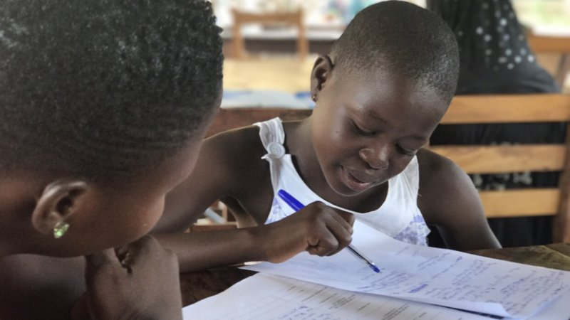 Young smiling Togolese girl pointing with a pin at her written action plan in a notebook.
