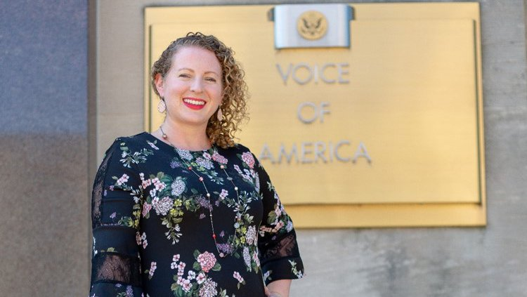 """A woman leans against a hand rail and smiles. Behind her is a plaque that says """"Voice of America"""""""