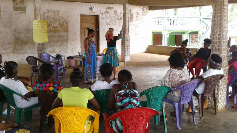 Peace Corps Volunteer Claire Hard teaches to a class of girls and women.