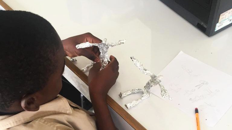 Jamaican Grade School Student sitting down and working on a sculpture of a man made out of foil in a white classroom