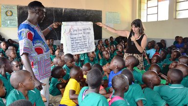 DCM & PC Staff reads out a big book for pupils.JPG