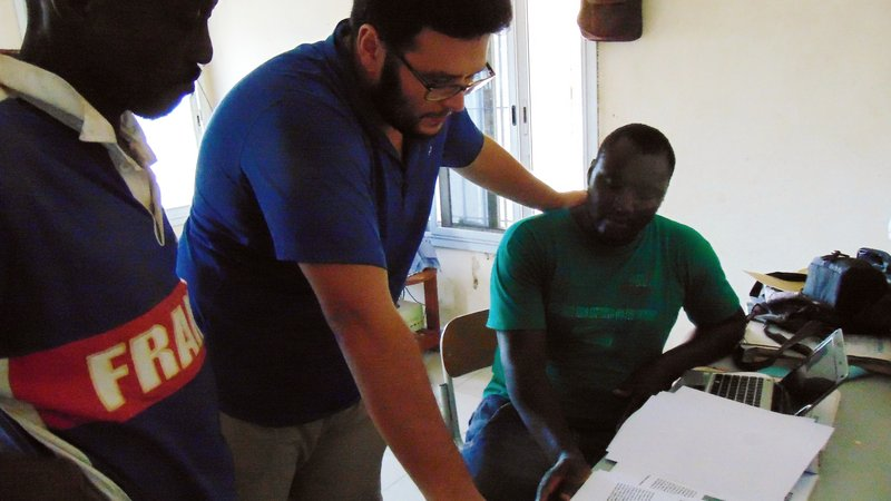 A male Peace Corps Volunteer points out data points to a male Senegalese coworker.