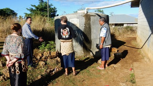 Rotary Club representative inspects tank with PCV couple and their principal
