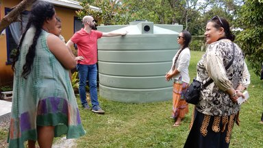 PC Volunteer and staff member visit site of a new water tank with US-AID representative,  visits site of a new