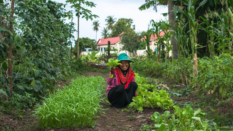 A woman with her newly-grown produce in her garden.