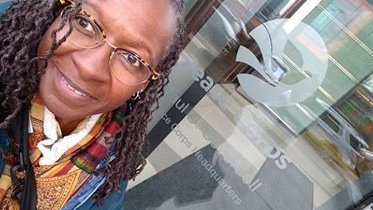 An older Black woman smiles for a selfie in front of a Peace Corps logo on a window.