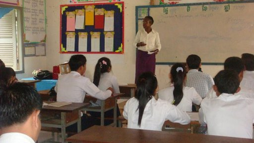 An older, Black woman stands in front of a classroom teaching Cambodian students.