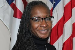 A Black woman smiles in front of an American flag for her professional head shot