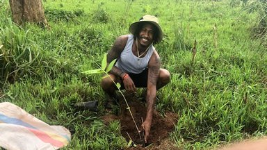 A Volunteer poses behind his newly planted bamboo seedling