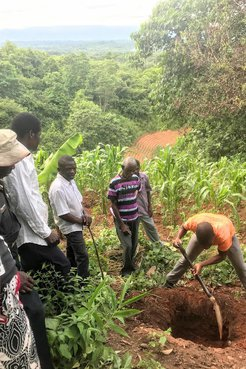 A group of community members stand around a large hill in a farm plot, preparing to plant a bamboo seedlings in its home
