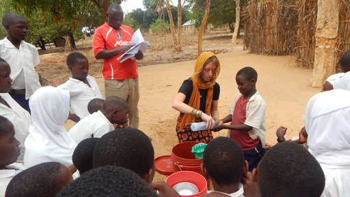 Emily's 6-year-old neighbor helping her demonstrate handwashing for the Mazingira Mazuri crowd after making a handwashing sta