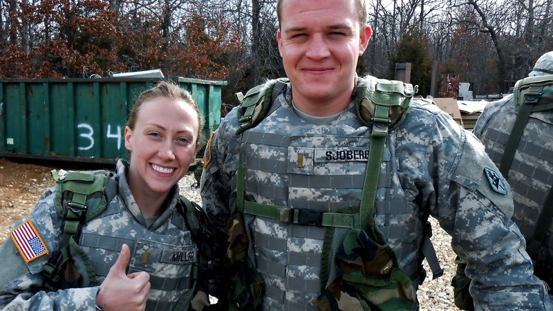An American male in army fatigues and a female American in army fatigues stand next to each other smiling.