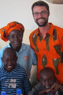 Peace Corps Volunteer Andrew Farr stands with a mother and her children.