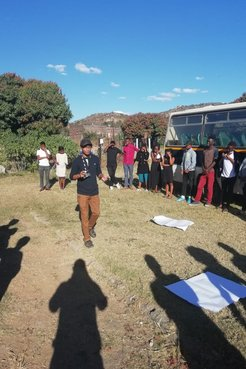 An male African American Peace Corps volunteer stands outside on the grass surrounded by South African teenagers next to a bu