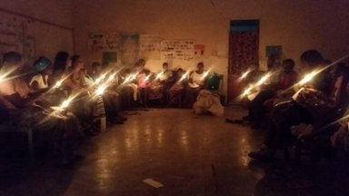 A group of Malawian girls participate in a candle lighting ceremony.