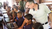 A teacher helps a student during computer class in Guyana
