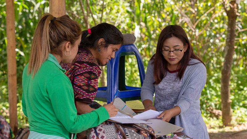 Hispanic female Peace Corps volunteer review paper documents with two female community members outside in Guatemala