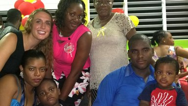 A Peace Corps Volunteer stands with her host family in Dominica.