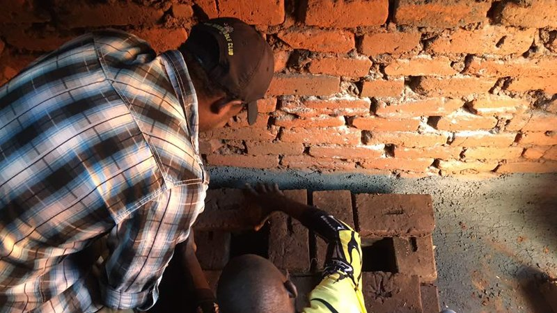 Justin and a community member construct a fuel-efficient cookstove