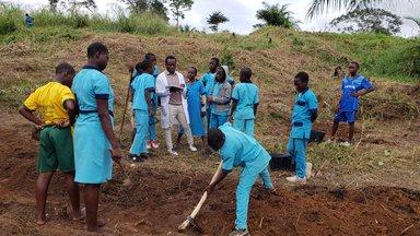 Students gather around teacher on the farm