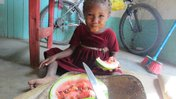 A young girl in Madagascar sits on the floor, smiling. There is a large piece of watermelon in her hand.