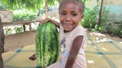 A young girl in Madagascar sits on a blanket next to a giant watermelon. She is smiling at the camera.