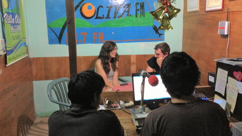 Three people from Paraguay and a white woman sit inside of a radio studio, doing interviews.