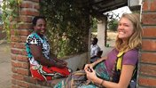 Volunteer Katlyn smiles at the camera while sitting on a brick porch with her smiling Malawian friend Katherine.