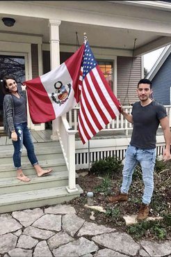 A man and a woman hold and American flag and a Peruvian flag outside of a house.