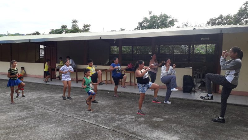 A black female teaches a group of Ecuadorian students how to kick box outside a classroom