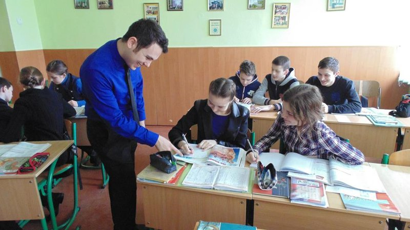 A Young white man leans over a desk to point something out to a younger student in Ukraine.