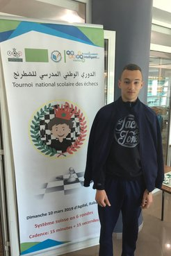 Ayman stands next to a large poster for a chess tournament