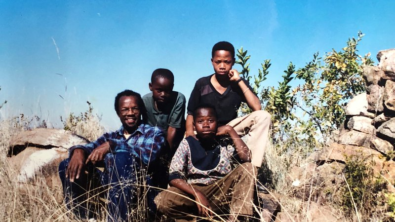 A middle aged black American man sits with two teenage South Africans on a hill outside.