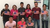 8 people holding up American flag