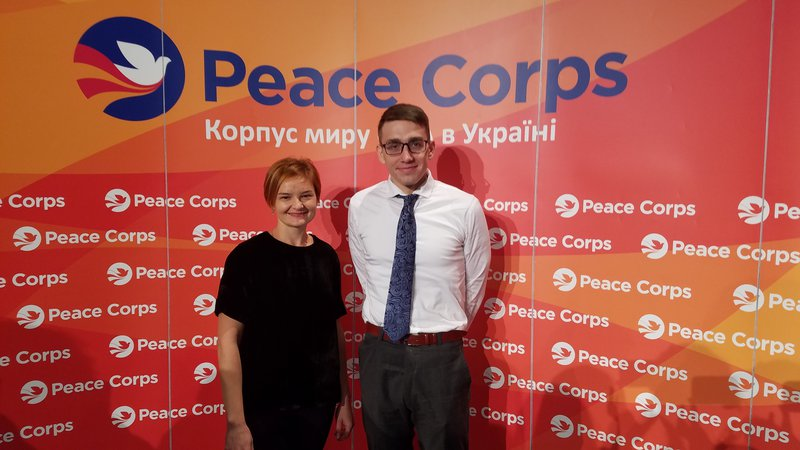 A man and a woman smile next to each other in front of a large orange Peace Corps banner.