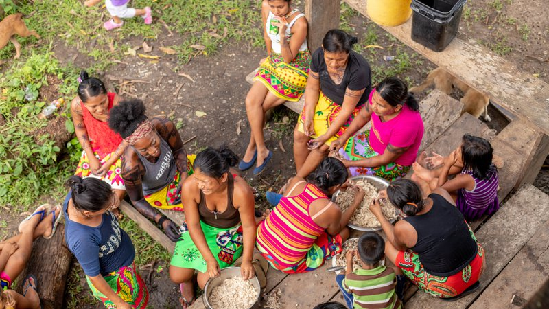 A young, Black American woman and her Panamanian friends sit outside cooking together