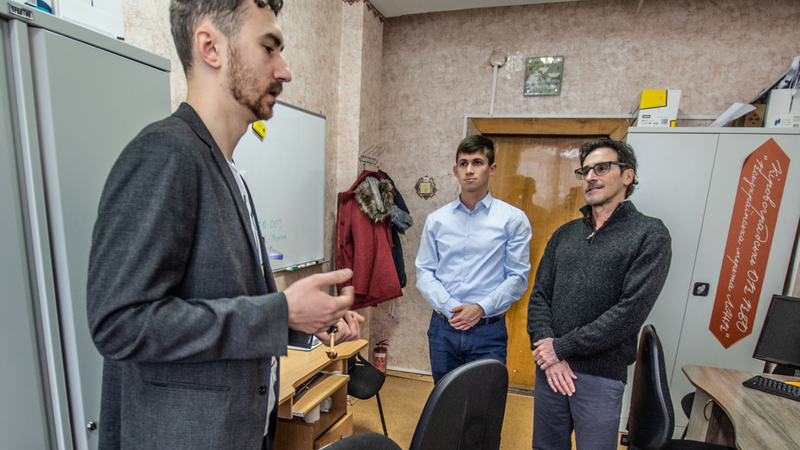 A young Ukrainian man stands speaking to two other men. He is dressed in a blazer.