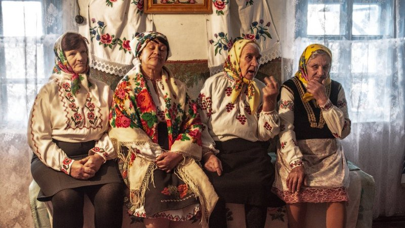 Four older Ukrainian women sit on a bench, wearing scarves on their heads and dressed in traditional clothing.